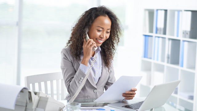 Asian business woman reading document and talking on the phone