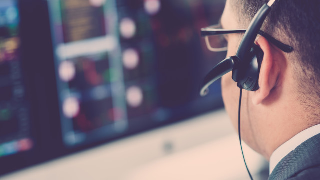 Close-up of broker in a headset analyzing data on the computer screen, selective focus